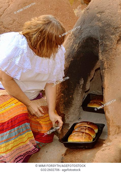 Woman baking bread in adobe horno, New Mexico, USA