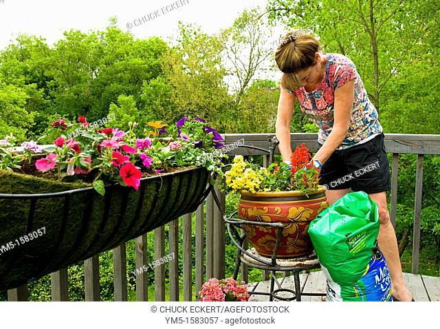 Woman potting flowers on back porch deck