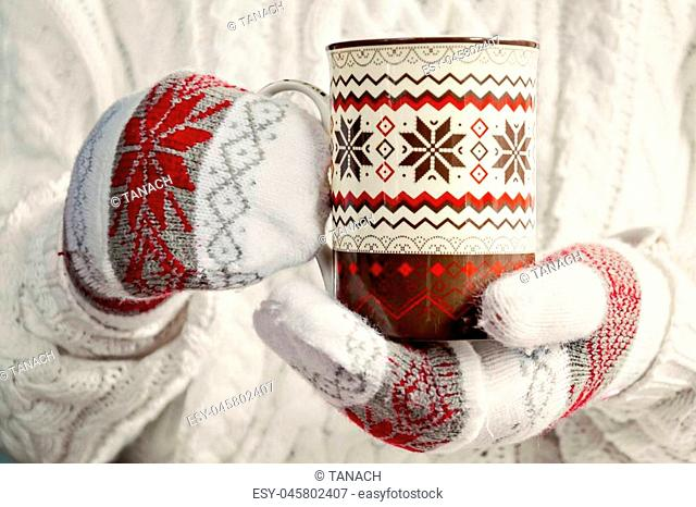 hands in mittens holding a cup of Scandinavian Christmas pattern close up