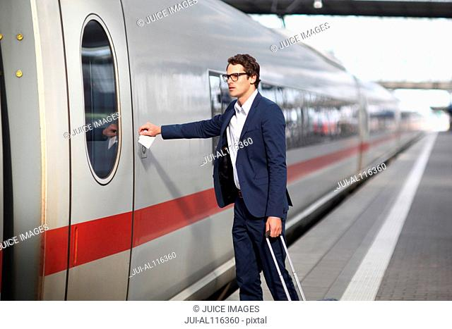 Mid adult business man reaching for train door, Munich, Bavaria, Germany, Europe