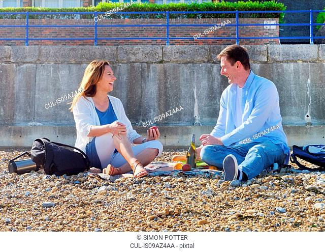 Couple having picnic on shingle beach