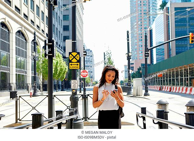 Businesswoman using cellphone by barriers