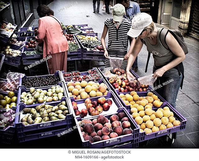 Women choosing fruit outside a grocery store