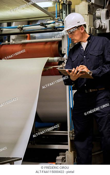 Factory worker writing on clipboard in factory