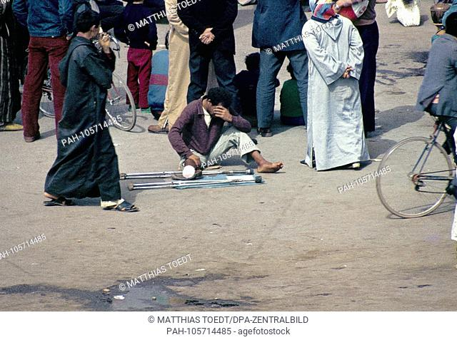 Leg amputee young beggar in the central market square Djemaa el Fna in Marrakech, unnoticed by the bystanders, analogue undated image of March 1985