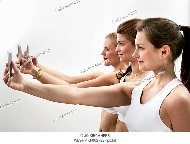 Row of three young woman taking selfie with their smartphones