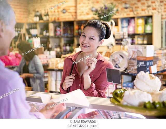 Smiling woman sampling cheese at deli counter in market