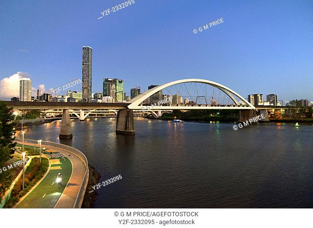 Railway bridge over Brisbane River with bicycle path and city skyline at dusk
