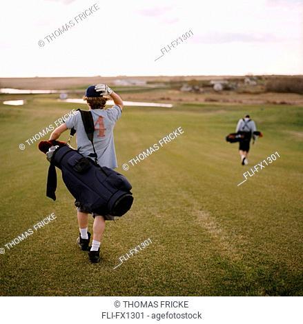 Men Carrying Golf Clubs on Course, Delisle, Saskatchewan