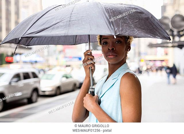 USA, New York, Portrait of young blonde african-american woman with umbrella