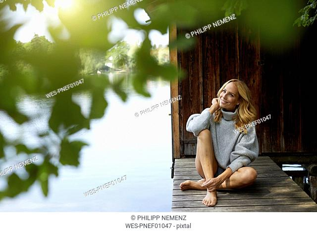 Smiling relaxed woman sitting on wooden jetty at a remote lake