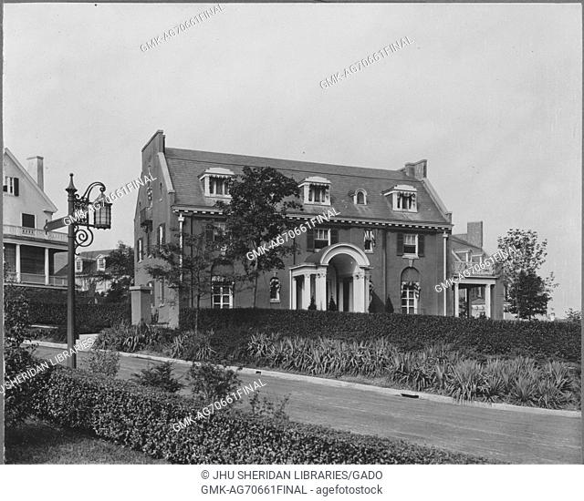 Landscape shot of a three story house, well-kept landscaping of trees, shrubs, and grass surrounding the house, decorated lamp post depicted