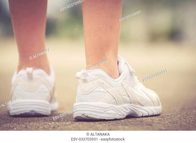 White youth sneakers on girl legs on road during sunny summer day