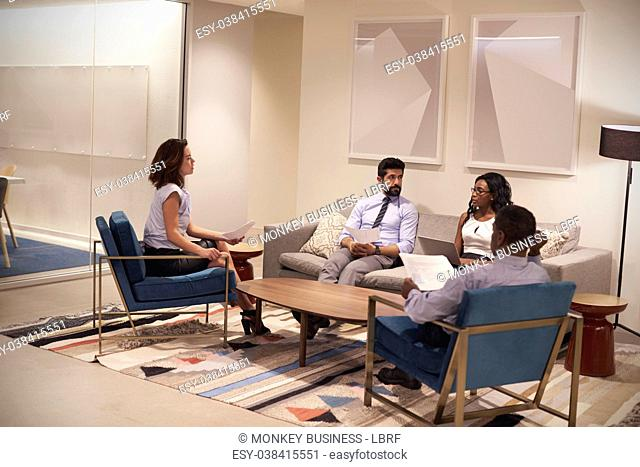 Four people meeting in lounge area of a corporate business