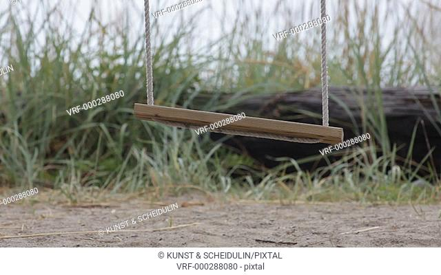 A wooden swing is moving slowly in the wind in front of a bay of the sea. Bönhamn, Västernorrlands Län, Sweden