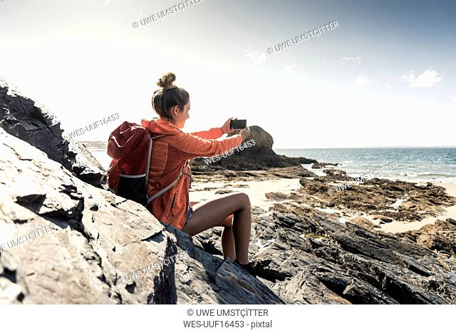 Young woman sitting on a rocky beach, using smartphone