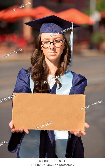 Graduate in blue gown holding a blank cardboard sign