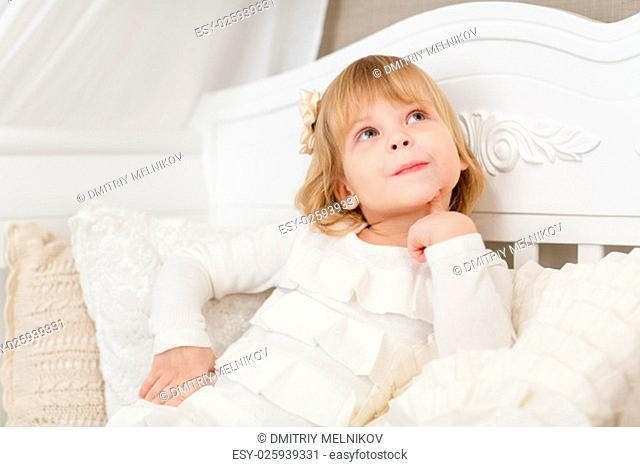 Happy pretty little girl sits on a sofa in the room