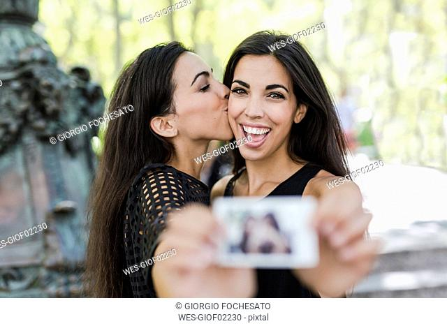 Two happy twin sisters holding an instant photo