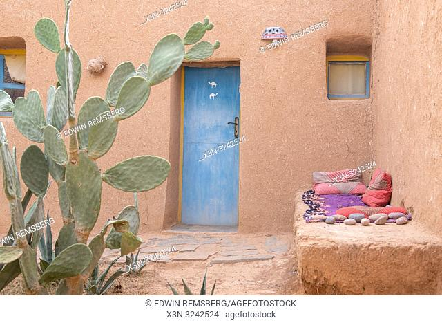 Exterior of mud-brick constructed house with blue door and cactus out in front, Tighmert Oasis, Morocco
