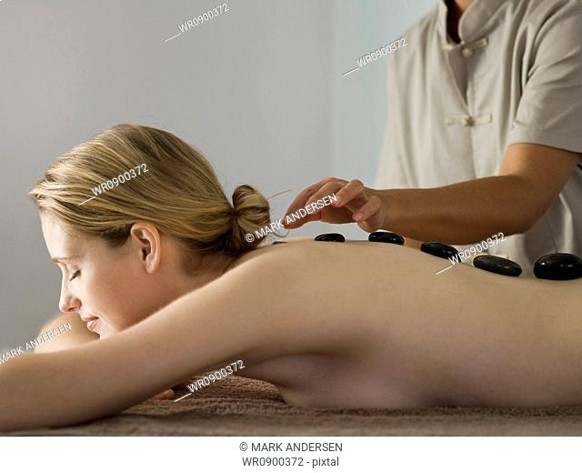 Woman placing black stones on womans spine