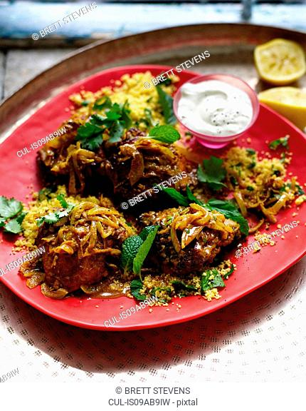 Plate of harissa chicken with couscous and mint yogurt