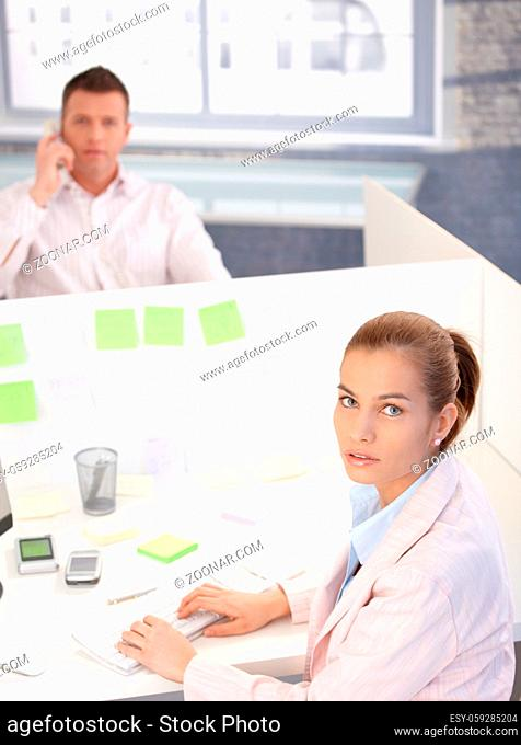 Attractive young woman working on computer in bright office, man on phone in the background