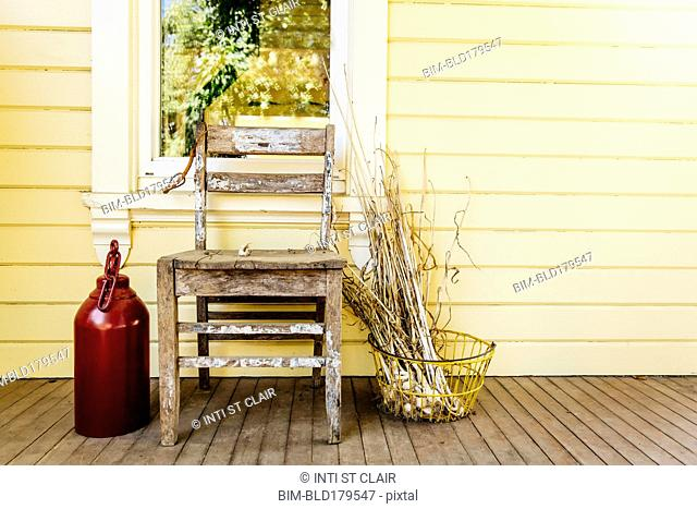 Chair with dried leaves and jug on porch