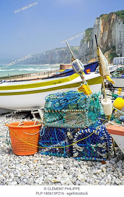 Traditional fishing boats / caïques and lobster pots on beach and sea cliffs at seaside resort Yport, Normandy, Seine-Maritime, Côte d'Albâtre, France