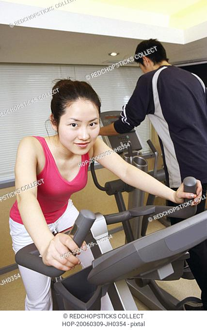 Close-up of a young woman exercising in a gym with a young man