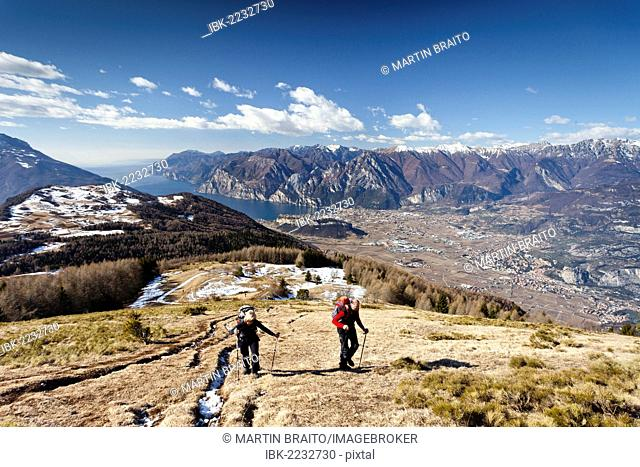 Hikers during the ascent to Monte Stivo Mountain above St. Barbara on Lake Garda, Lake Garda with the village of Riva at the rear and the village of Arco below