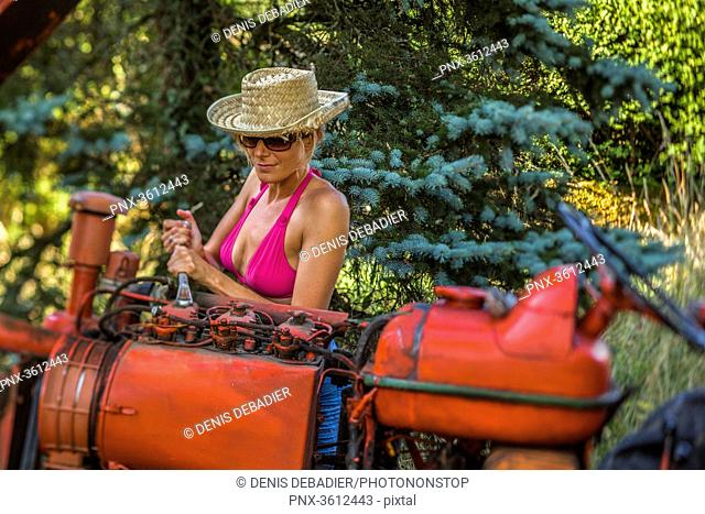 Sexy women repairing the tractor engine in the countryside