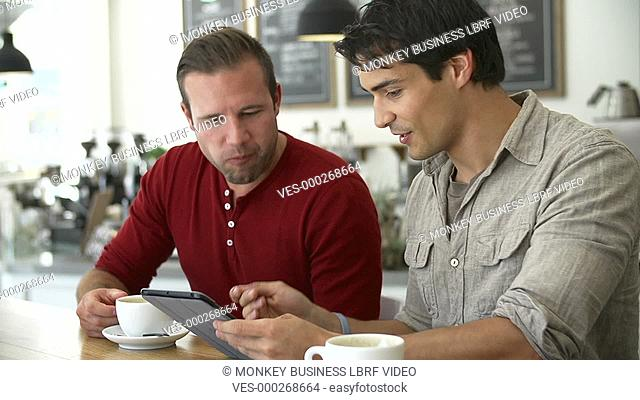Two male friends sitting at table in café looking at digital tablet.Shot on Sony FS700 in PAL format at a frame rate of 25fps
