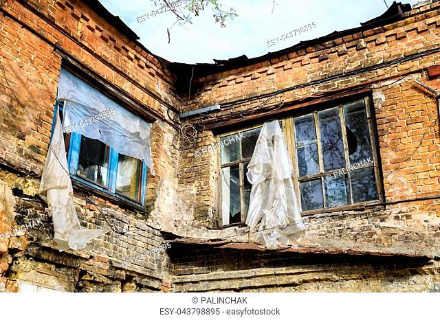 Broken windows with polyethylene film instead of glasses on the old abandoned brick building in Kiev, Ukraine