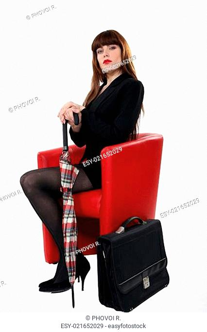 Brunette sat in chair with umbrella and briefcase