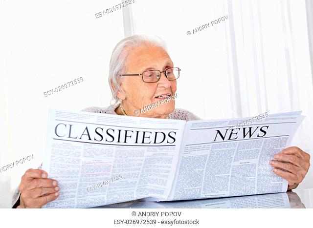 Happy Senior Woman Reading Newspaper On Desk At Home