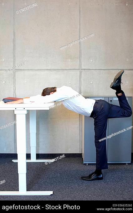 yoga in office. business man exercising at electric height adjustable desk in office - stretching at desk