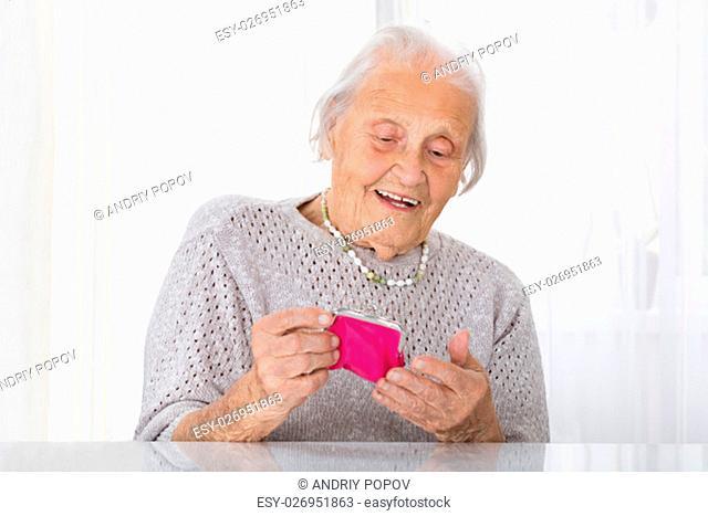 Portrait Of Happy Senior Woman Holding Small Purse