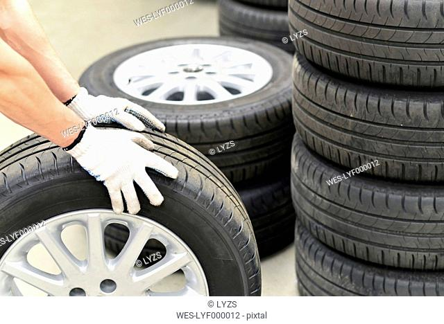 Close-up of car mechanic with tires