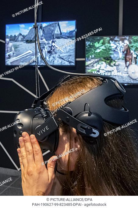 """24 June 2019, Baden-Wuerttemberg, Karlsruhe: A user of the exhibition """"""""Archaeology in Baden - Expothek¹"""""""" is wearing VR glasses in the Expolab"""