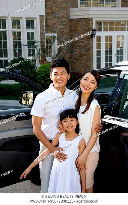 Oriental family standing be car in front of villa