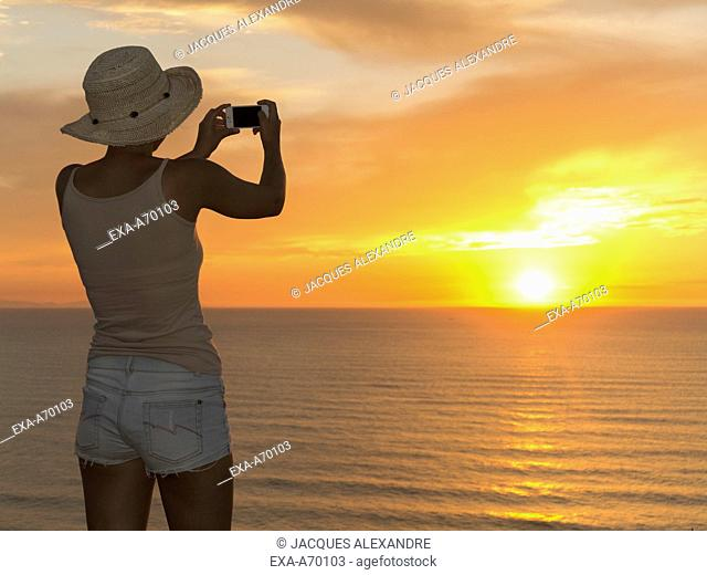 Woman with sun hat, back view, photographing sunset at sea