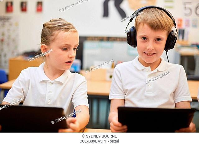 Schoolboy listening to headphones in class at primary school, portrait