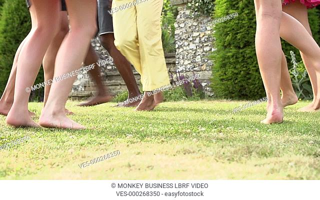 Slow motion sequence of feet moving on grass in summer garden.Shot on Sony FS700 in PAL format at a frame rate of 50fps