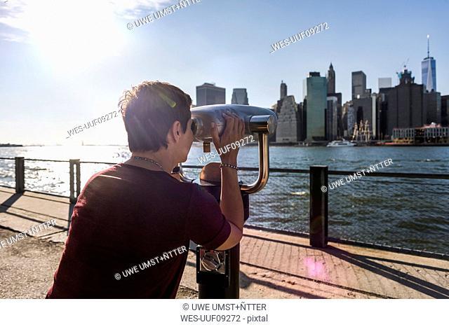 USA, Brooklyn, woman looking at Manhattan skyline with coin operated binoculars