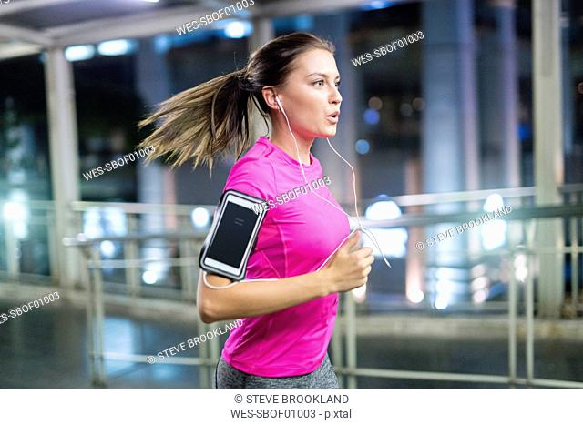 Young woman in pink sportshirt running in city at night