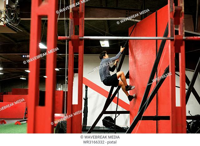 Muscular man climbing a wall with rope