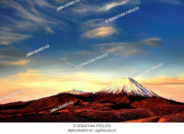 The cone of the Mt. Ngauruhoe in the Tongariro national park. The volcano is overcast with snow during a magnificent sundown