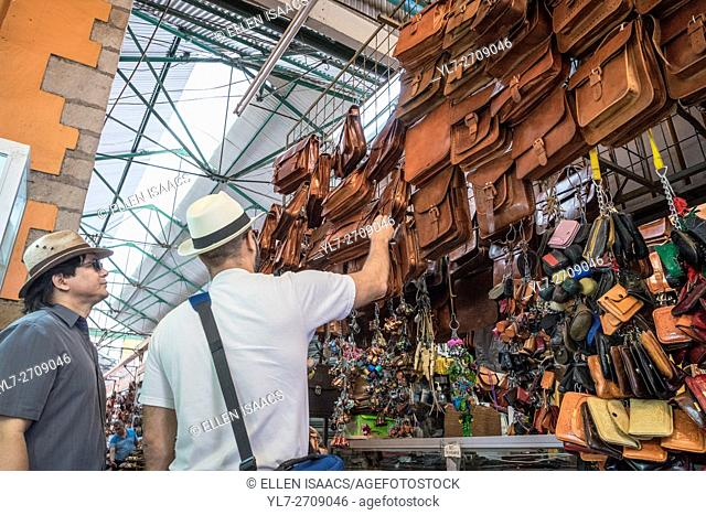 Two men shopping for leather bags at a stall in the Benito Juarez Market in Oaxaca Mexico