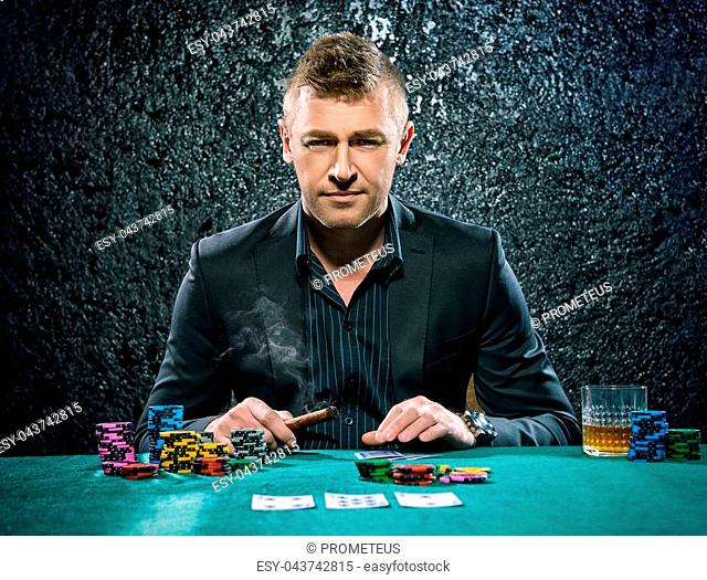 Rich gambler man with the cards and chips in casino. Gambling, playing cards and roulette